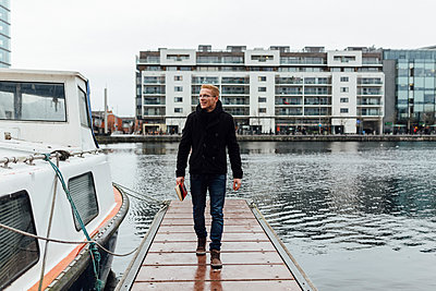 Ireland, Dublin, smiling young man with a book walking on a jetty in winter - p300m1120769f by Boy photography