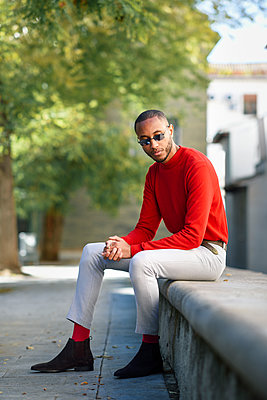 Portrait of fshionable young man wearing red pullover and sunglasses sitting on stone bench - p300m2070096 von Javier Sánchez Mingorance