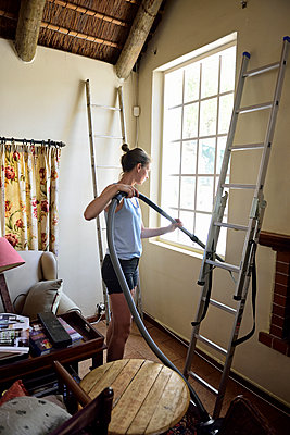 Young woman renovating her home hoovering - p300m2079470 by Eyecatcher.pro