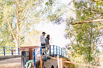 A couple with their dog standing on a bridge in a park - p300m2166358 by Daniel González