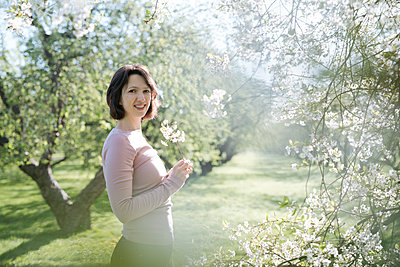 Portrait of smiling woman with twig of blossoming cherry tree at sunlight - p300m2166421 by Ekaterina Yakunina