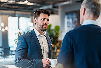 Mid adult businessman talking with male colleague in office cafe - p300m2273899 by Daniel Ingold