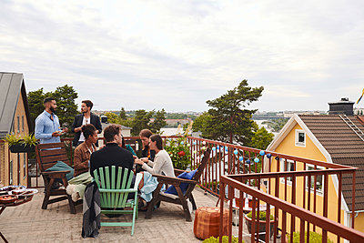 Friends talking while spending leisure time on terrace against sky - p426m2074305 by Maskot