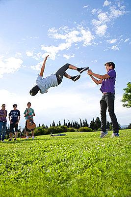 Teen boys help friend to do a flip - p4292905f by Britt Erlanson