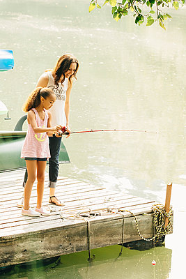 Mother and daughter fishing in lake - p555m1306255 by Inti St Clair