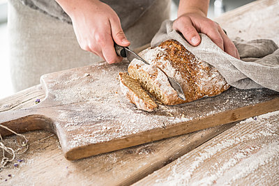 Cutting freshly baked bread - p936m1161852 by Mike Hofstetter