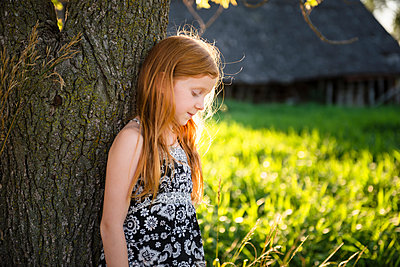 Young girl with red hair standing by tree, barn in background. - p1166m2290270 by Cavan Images