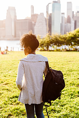 USA, New York City, Brooklyn, woman standing on meadow looking at the skyline - p300m1499341 by Giorgio Fochesato