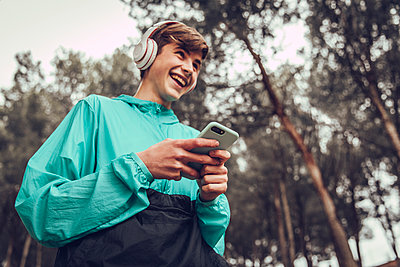Teenager with headphones wearing raincoat in the forest - p300m2202414 by Aitor Carrera Porté