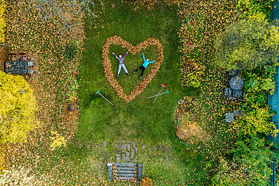 People lying in heart made out of fallen leaves - p312m2118564 by Johner