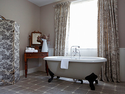 Grey patterned fabrics and claw foot bath in Edwardian school house bathroom conversion - p349m789858 by Brent Darby