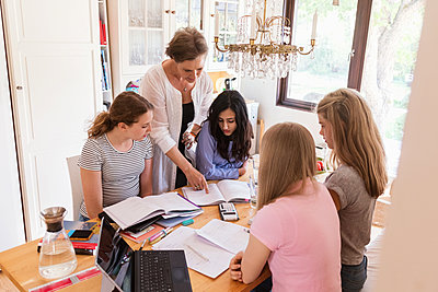 Woman assisting teenage girls in doing homework at home - p426m1196492 by Maskot
