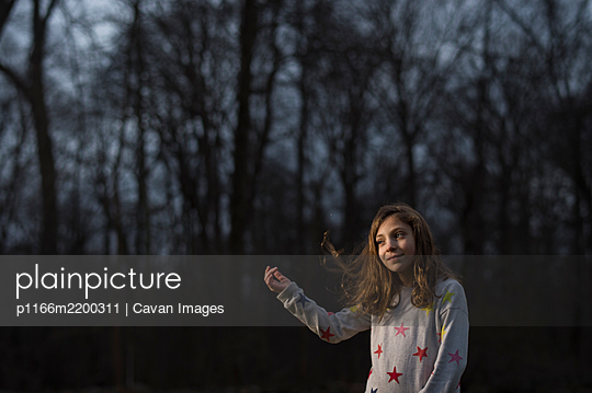 Girl flipping her hair in golden hour light - p1166m2200311 by Cavan Images