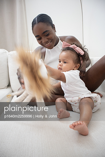Mother and daughter playing with cuddly toy - p1640m2259996 by Holly & John