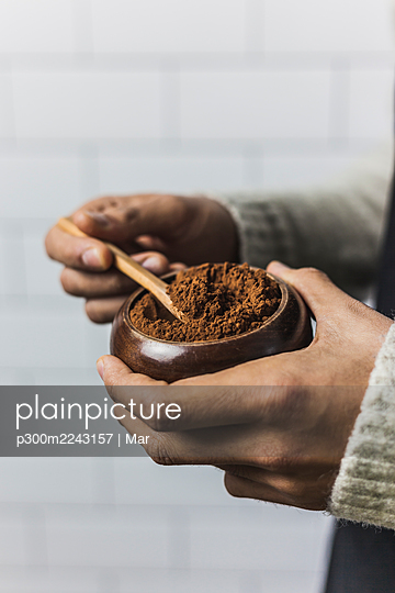 Hands of man holding bowl of cocoa powder - p300m2243157 by Mar
