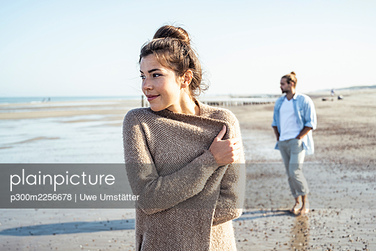Girlfriend and boyfriend looking away while standing on beach during sunny day - p300m2256678 by Uwe Umstätter