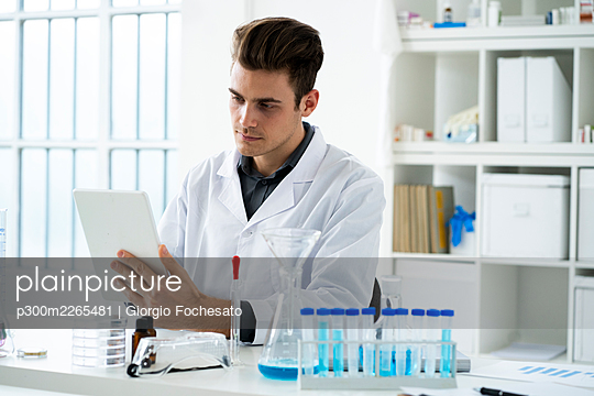 Serious male scientist holding digital tablet while working in laboratory - p300m2265481 by Giorgio Fochesato