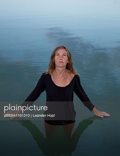 Junge Frau im Wasser blickt nach oben  - p552m1161310 von Leander Hopf
