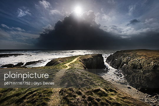 A day of mixed weather, brilliant sunshine and violent hail showers over the Irish Sea on the West coast of Anglesey, Wales, United Kingdom, Europe