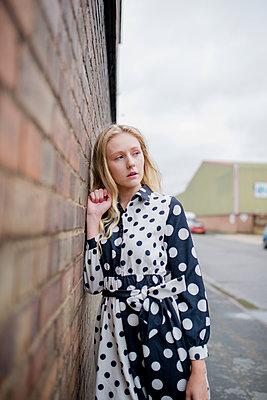 Junge Frau an einer Wand - p1628m2195855 von Lorraine Fitch