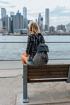 USA, New York City, Brooklyn, young woman sitting at the waterfront with backpack, headphones and tablet - p300m2069410 von Boy photography