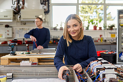 Portrait of smiling female electrician working on circuitry in workshop - p300m2181227 by Zeljko Dangubic