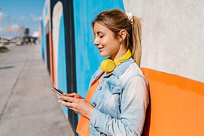 Blond woman using smart phone against wall - p300m2274413 by Ezequiel Giménez