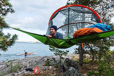 Man resting in hammock at lakeshore - p312m2049795 by Fredrik Schlyter