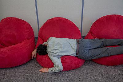 Mann liegt auf Sitzsäcken - p397m1588942 von Peter Glass