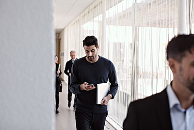 Businessman using smart phone while walking with colleagues in corridor during leaving office - p426m2117019 by Maskot