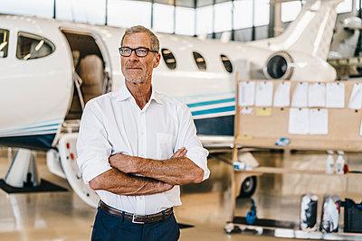 Mature businesman in aeroplane hangar - p586m1208521 by Kniel Synnatzschke