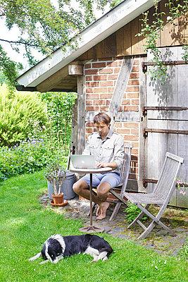 Mann mit Laptop im Garten - p606m933985 von Iris Friedrich