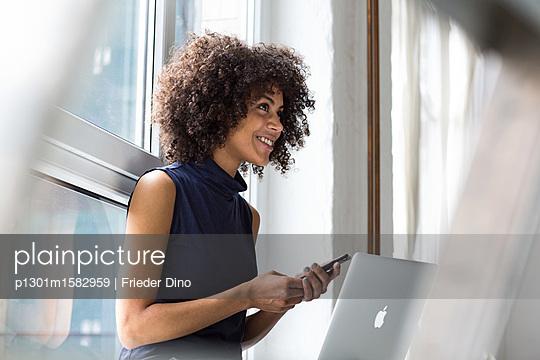 Geschäftsfrau sitzt mit ihrem Laptop auf einer Fensterbank  - p1301m1582959 von Delia Baum