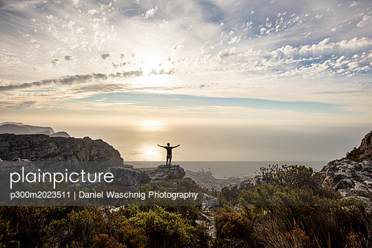 South Africa, Cape Town, Table Mountain, man standing on a rock at sunset - p300m2023511 von Daniel Waschnig Photography