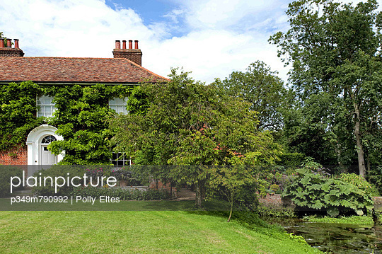 Lawned garden exterior of rural brick Suffolk country house - p349m790992 by Polly Eltes
