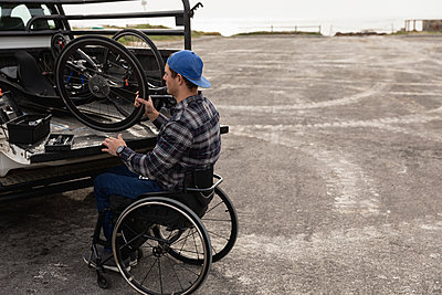 Disabled man in a wheelchair taking bike out of a car - p1315m2131524 by Wavebreak