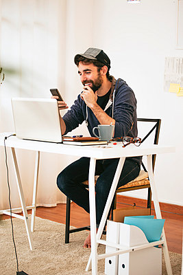Man with smartphone at modern home office - p300m929823f by Bonninstudio