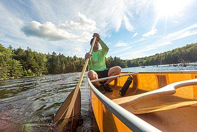 Man paddling in canoe through pond, Woodford, Vermont, USA - p343m1543661 by Matt Andrew