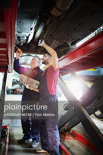 Male mechanics working under car in auto repair shop - p1023m2196748 by Tom Merton