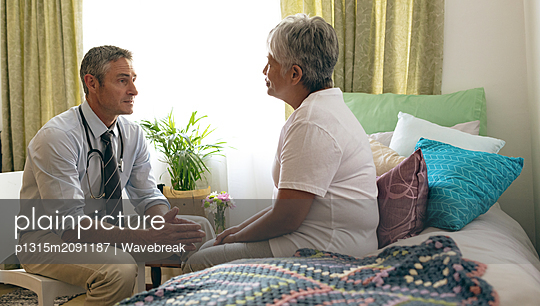 Male doctor interacting with senior female patient at retirement home - p1315m2091187 by Wavebreak