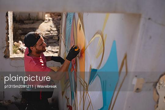 Graffiti artist spray painting on weathered wall room - p1315m2091211 by Wavebreak