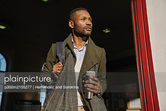 Stylish man with reusable cup getting out of the train station - p300m2155277 by Hernandez and Sorokina