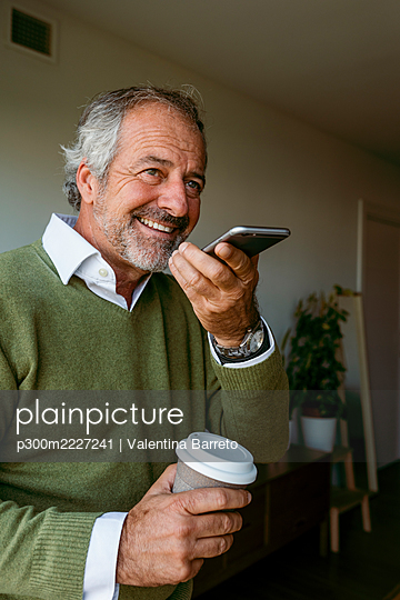 Smiling man with coffee cup talking on mobile phone while standing at home - p300m2227241 by Valentina Barreto