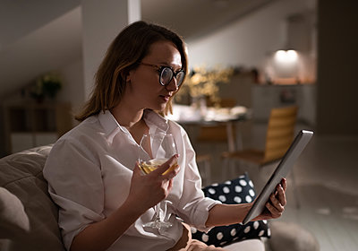 Young woman with glass of wine using tablet at home - p1166m2234321 by Cavan Images