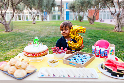 Little boy with golden balloon behind laid birthday table - p300m1189585 by Valentina Barreto