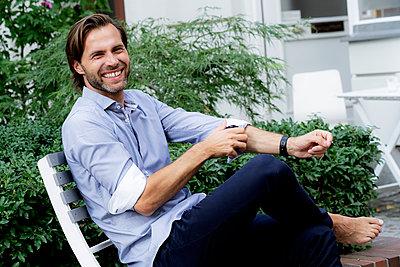 Portrait of happy man sitting on chair in garden - p300m2042007 by harrylidy