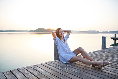 Portrait of mature woman sitting on jetty at a lake at sunrise - p300m2140664 by Philipp Nemenz
