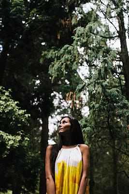 Junge Frau im gelben Kleid steht in einem Wald - p586m953782 von Kniel Synnatzschke