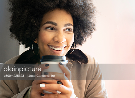 Smiling afro woman drinking coffee while sitting at cafe - p300m2253231 by Jose Carlos Ichiro