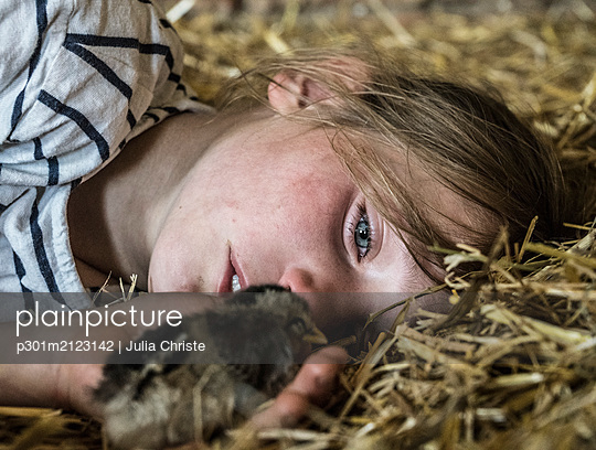 Close up girl holding baby chick in straw - p301m2123142 by Julia Christe